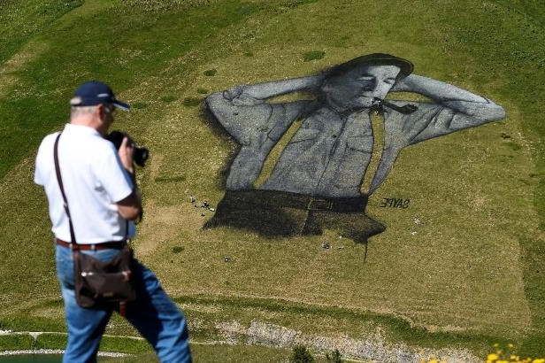 A man photographs a work by French artist Saype and said to be the world's largest biodegradable painting on the Chaux-de-Mont ski slope above the Alps resort of Leysin, Switzerland on August 4, 2016