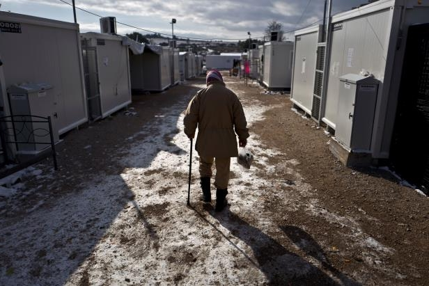 An elderly Syrian refu­gee walks to his shelter on frozen ground at the Ritsona refugee camp.