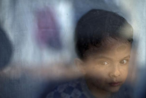 "Migrant Petram Mehdi, 2, from Tehran, stands by the window of his family's shelter at the Ritsona refugee camp on Jan. 12. The European Commission says conditions for the refugees are ""untenable"" during the winter."