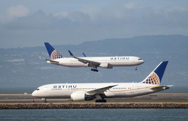 A United Airlines Boeing 787 taxis as a United Airlines Boeing 767 lands at San Francisco International Airport, San Francisco, California, on February 7, 2015.
