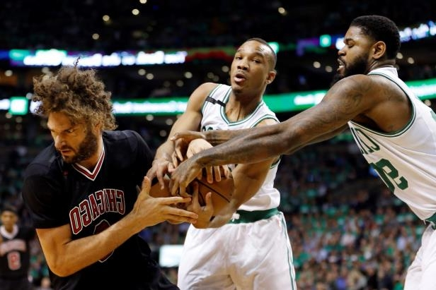 Slide 1 of 26: Boston Celtics guard Avery Bradley (0) and Boston Celtics center Amir Johnson (90) battle with Chicago Bulls center Robin Lopez (8) during the first quarter in game two of the first round of the 2017 NBA Playoffs on April 18 in Boston, MA.