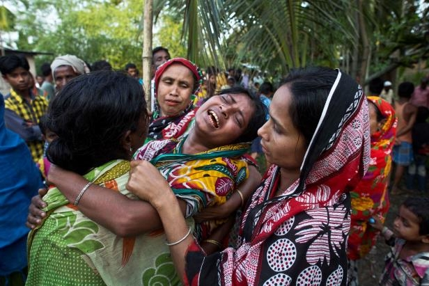 Relatives of Abu Hanif, who was beaten to death by a mob on Sunday night, wail during his funeral in Naramari village, about 140 kilometers east of Gauhati, in the northeastern Indian state of Assam, Monday, May 1, 2017. Two Muslim men, including Hanif, were beaten to death by a mob in northeastern India over allegations of cow theft, the latest in a series of similar attacks across the country, police officials said Monday. Human Rights Watch said in a report last week that since Prime Minister Narendra Modi's government took office at least 10 Muslims, including a 12-year-old boy, have been killed in mob attacks in seven separate incidents related to allegations over cows. (AP Photo/Anupam Nath)