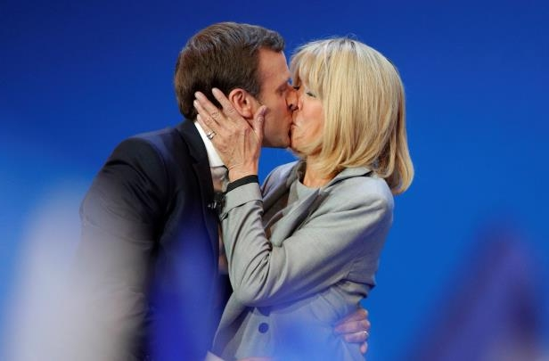 FILE - In this April 23, 2017 file photo, French centrist presidential candidate Emmanuel Macron kisses his wife Brigitte before addressing his supporters at his election day headquarters in Paris. Brigitte Macron, the woman would could become France's next first lady not only lives a singular love story with her 24-year-younger husband, she is also his closest collaborator and plays a major role in his campaign. (AP Photo/Christophe Ena, File): French presidential candidate Emmanuel Macron kisses his wife Brigitte at his election day headquarters in Paris.