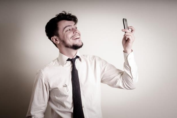 "Young businessman taking photo with phone on gray background: ""Narcissists have an empathy deficit disorder – they're not capable of empathy as we know it."""
