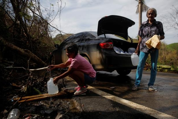 People affected by Hurricane Maria fill up water jugs from a mountain drain near the municipality of Morovis, outside San Juan, Puerto Rico, Oct. 10, 2017