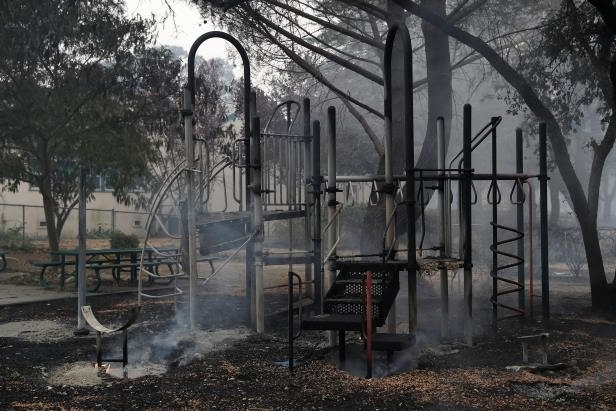 Slide 7 of 28: Smoke rises from a playground in front of Dunbar Elementary School during the Nuns Fire in Sonoma. REUTERS/Stephen Lam