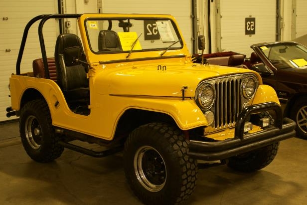 a yellow and black truck parked in a parking lot: jeep cj
