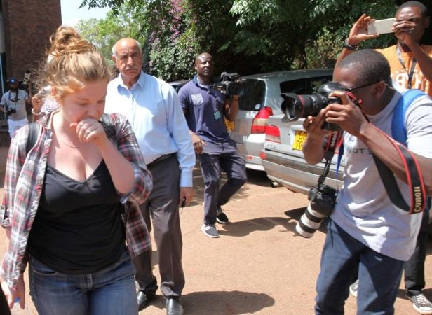 a group of people walking down the street talking on a cell phone: U.S. citizen Martha O'Donovan arrives at court in Harare