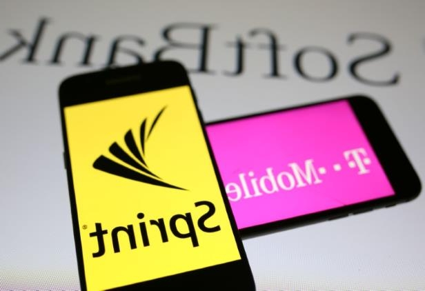 a close up of a sign: Smartphones with the logos of T-Mobile and Sprint are seen in front of a Soft Bank logo in this illustration