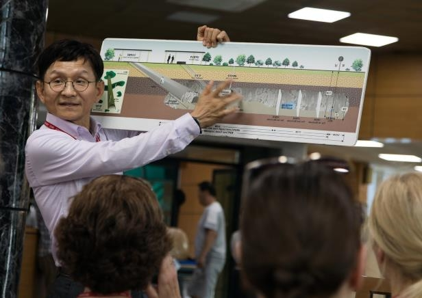 a group of people standing in front of a crowd: A South Korean tour guide showing a map of one of the tunnels.