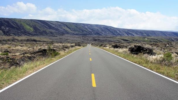 a long road with grass on the side of a mountain: Rural Highway – Single Broken Yellow Line