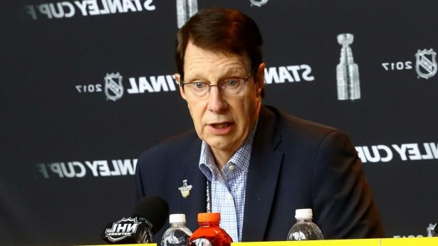 a man holding a sign: David Poile