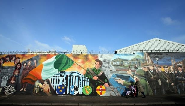 A woman walks past murals on the Falls Road in Belfast, Northern Ireland depicting images related to the province's conflicts with the Republic of Ireland; sectarian tensions remain between Catholic Irish nationalists and Protestant British unionists