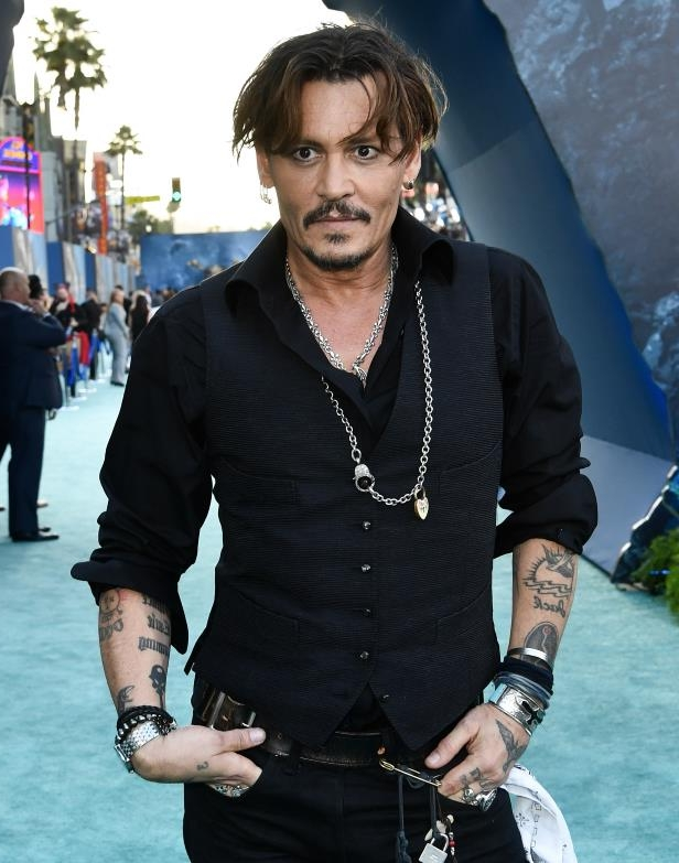 a man wearing a suit and tie: Johnny Depp attends the premiere of