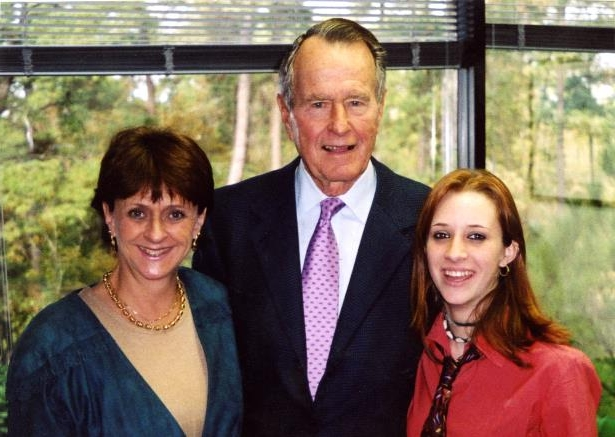 George H. W. Bush et al. posing for the camera: Roslyn Corrigan (L), former president George H.W. Bush (C) and Sari Young (R) at the November 2003 event where Corrigan says Bush groped her.