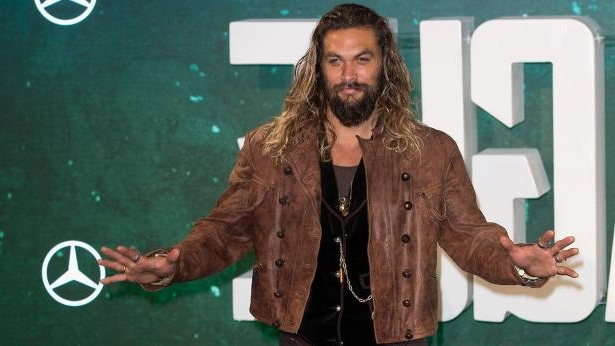 Jason Momoa holding a sign posing for the camera