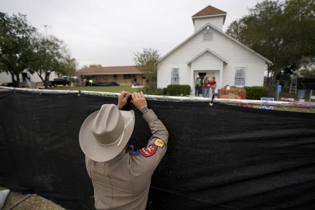 Slide 1 of 61: A Texas state trooper helps erect a fence around the site of the shooting at the First Baptist Church of Sutherland Springs, Texas, U.S. Nov. 9.