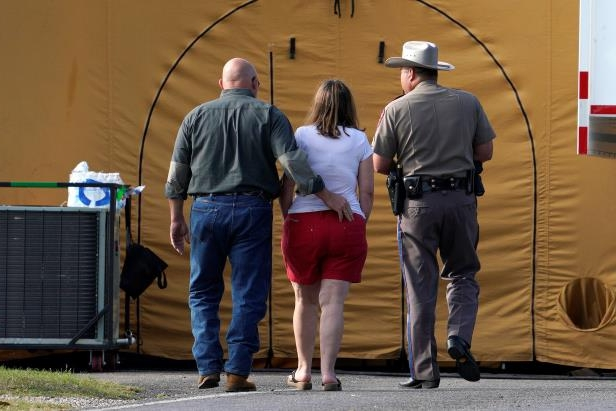 Slide 10 of 61: A woman is escorted to site of a shooting at the First Baptist Church of Sutherland Springs, Texas, U.S. November 6, 2017.