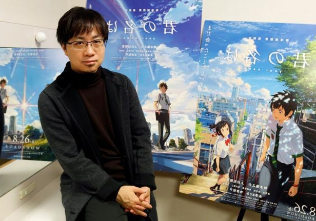 Slide 18 of 28: FILE PHOTO - Japanese anime director Makoto Shinkai poses for a photo in front of posters of his animated film 'Your Name' after an interview with Reuters in Tokyo