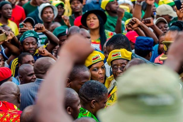a group of people standing in front of a crowd: President Robert Mugabe and his wife, Grace, arrived at ZANU-PF party headquarters last week during a rally in support of Mrs. Mugabe becoming the next vice president.
