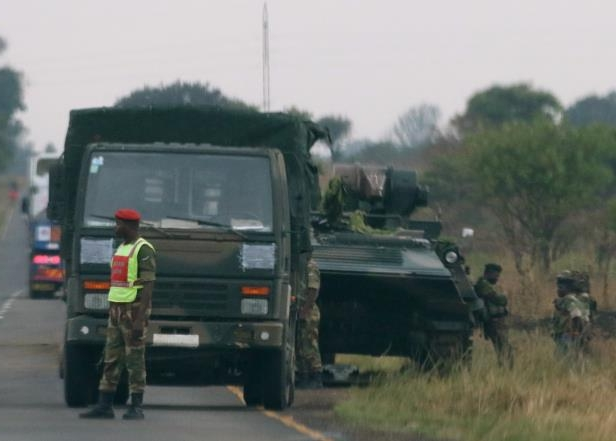 Soldiers stand beside military vehicles just outside Harare, Zimbabwe November 14, 2017.