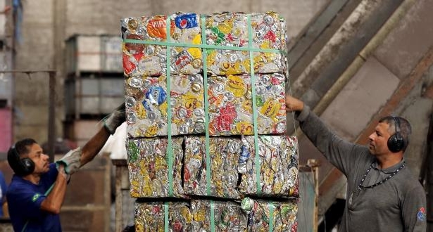 Two men inspect blocks of recycled aluminum