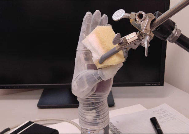 person sitting at a desk with a laptop: University of Utah researchers have developed technology that allows users to feel through this robotic arm. In one experiment, they were able to use the hand to distinguish soft foam from hard plastic.