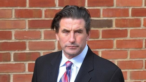 William Baldwin in a suit standing in front of a brick wall: Billy Baldwin criticized Trump's