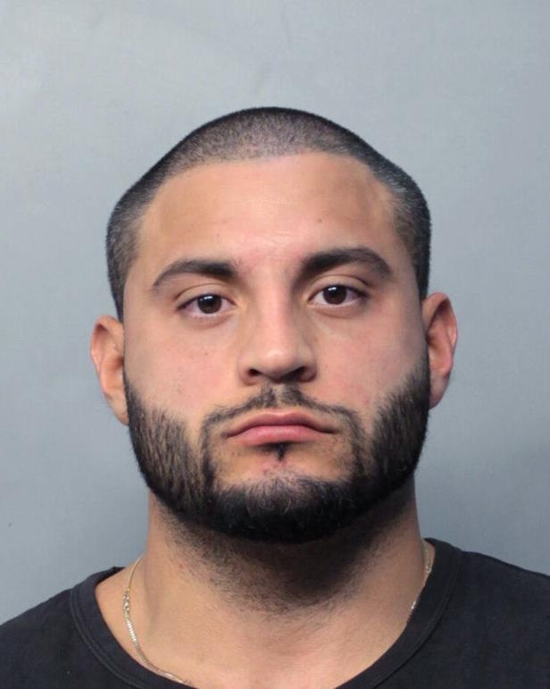 This photo made available by the Miami Dade Police Department shows 32-year-old Michael Arana under arrest, Thursday, Nov. 30, 2017 in Miami. Arana is the head of security for singer Justin Bieber. He was arrested in Miami following a car crash that injured two police officers. (Miami Dade Police Department via AP)