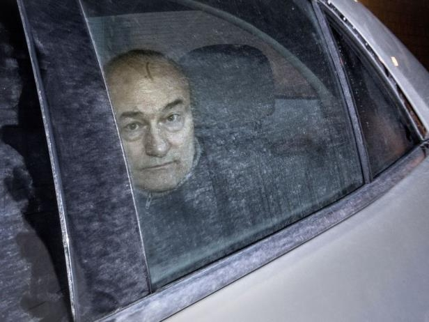 Ian Bush inside the back of of an unmarked police cruiser as it leaves the Elgin St. courthouse in Ottawa, Friday, February 20, 2015.