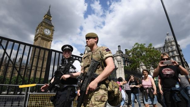 Armed soldier and armed police officer patrol outside Westminster Palace