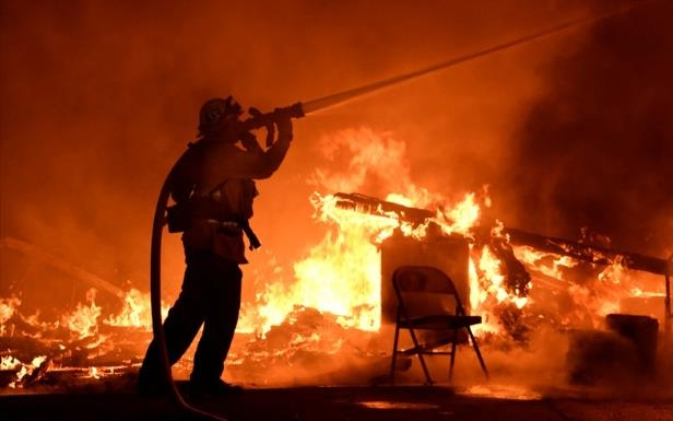 a fire burning in a dark room: Firefighters battle flames from a Santa Ana wind-driven brush fire called the Thomas Fire in Santa Paula, California