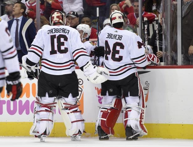 Chicago Blackhawks goalie Anton Forsberg (31), of Sweden, leaves the game after giving up three goals during the first period of an NHL hockey game against the Washington Capitals, Wednesday, Dec. 6, 2017, in Washington. Also seen is Chicago Blackhawks goalie J.F. Berube (34), who replaced Forsberg. (AP Photo/Nick Wass)