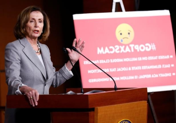 Nancy Pelosi holding a sign posing for the camera: House Minority Leader Nancy Pelosi speaks about tax reform during a press conference on Capitol Hill in Washington