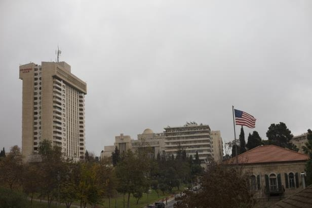 a city with tall buildings in the background: An American flag flies over the U.S. Consulate General building on Dec. 6 in Jerusalem. (Lior Mizrahi/Getty Images)