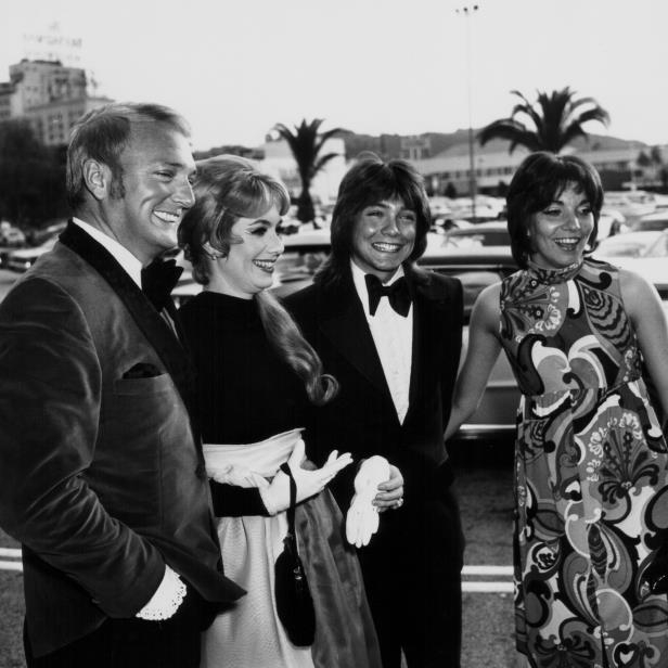 Slide 4 of 14: <p>Cassidy's Partridge Family mom was played by his real-life stepmother Shirley Jones, who married Cassidy's father in 1956. Cassidy (center) attended the 1975 Grammy Awards with (from left) his date Lynn Dubiou, Jones and his father.</p>
