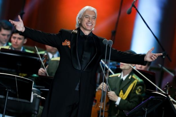 Slide 9 of 181: Baritone Dmitri Hvorostovsky (front) acknowledges the audience as he performs with the Song and Dance Ensemble of the Russian Interior Ministry in a concert titled 'Songs of the War Years' at the Green Theatre of the VDNKh Exhibition Centre on Victory Day.
