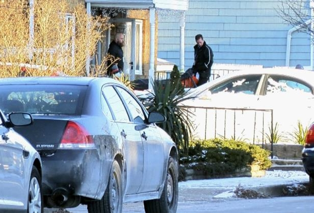 Authorities remove a body from a home in Long Branch, N.J., Monday, Jan. 1, 2018. A 16-year-old has been arrested after his parents, sister and a family friend were found dead inside the home where they lived, authorities said Monday.