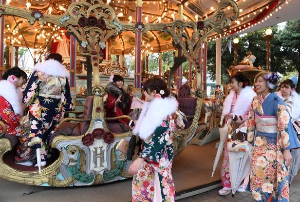 20-year-old women wearing kimonos ride a carousel after their