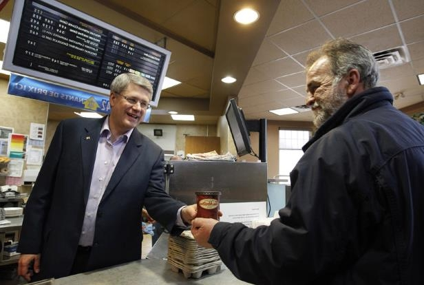 a man standing in front of a store: Stephen Harper works behind the counter during a campaign stop at a Tim Hortons in Dieppe, N.B., April 1, 2011. Canadians went to the polls in a federal election May 2. (Chris Wattie/Reuters)