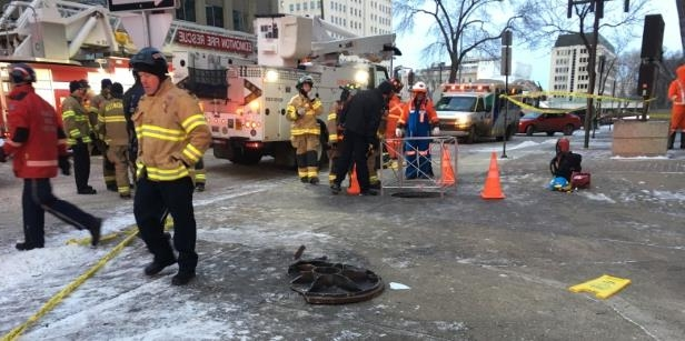 a group of people walking down a street: A person fell down a manhole in downtown Edmonton Wednesday morning after an underground explosion shook parts of the city's centre.