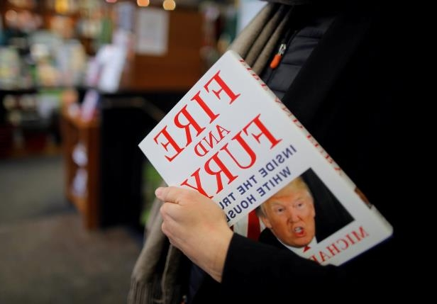 person holding a sign: Anti-Trump lowbrowism burst into full bloom with the new Michael Wolff book.