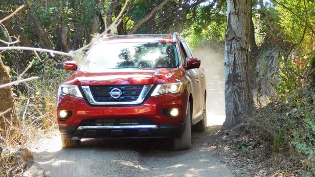 a car parked on pavement near a forest: 2017 Nissan Pathfinder Platinum 4WD