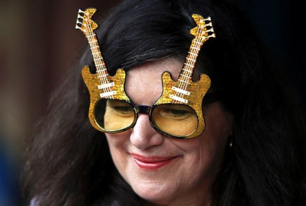 a close up of sunglasses: An Elvis Presley fan wears glasses shaped in the form of guitars as she prepares to board the Elvis Express train at Sydney's Central station before it departs for the 26th annual Elvis Festival