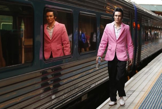 a group of people standing in a train station: Elvis Presley impersonator Finlay walks alongside the Elvis Express train at Sydney's Central station before it departs for the 26th annual Elvis Festival