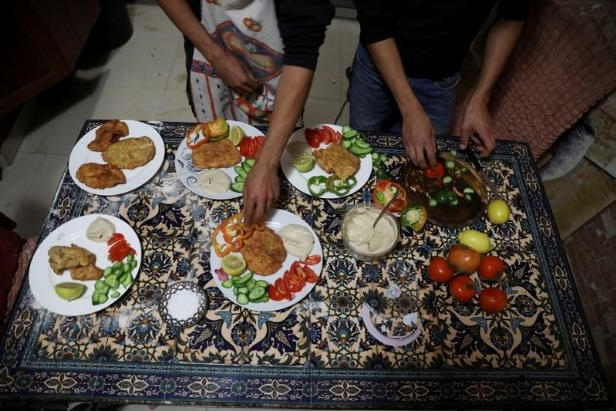 a man holding a plate of food: The Wider Image: Palestinians in East Jerusalem cherish their horses