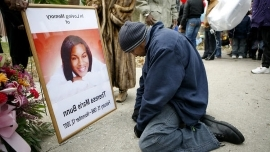 a man holding a sign: Loree Williams prays in front of a photo of his cousin Theresa Bunn during a vigil near Washington Park on Chicago's South Side — at the site where her strangled body was found in 2007.
