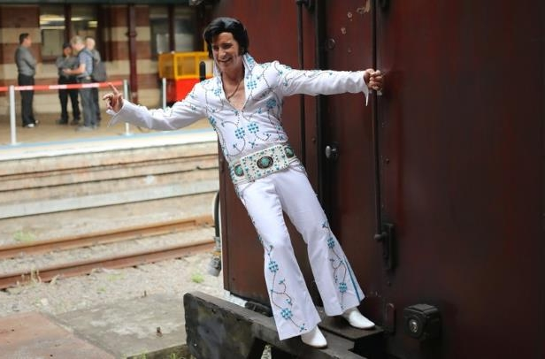 a person posing for the camera: An Elvis Presley impersonator hangs from the Elvis Express train at Sydney's Central station before it departs for the 26th annual Elvis Festival