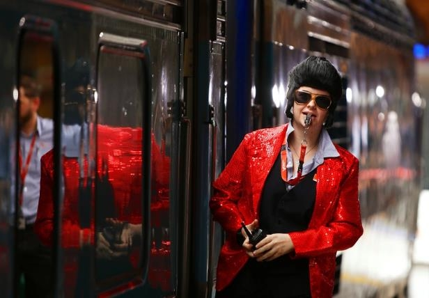 a woman standing in front of a store: A train guard dressed as Elvis Presley blows a whistle to signal the departure of the Elvis Express train at Sydney's Central station bound for the 26th annual Elvis Festival being held in the New South Wales town of Parkes