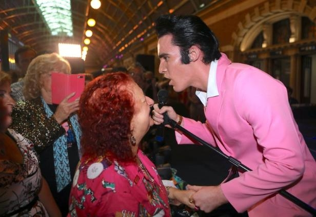 a man sitting on a table: Elvis Presley impersonator Finlay greets onlookers before boarding the Elvis Express train at Sydney's Central station before it departs for the 26th annual Elvis Festival